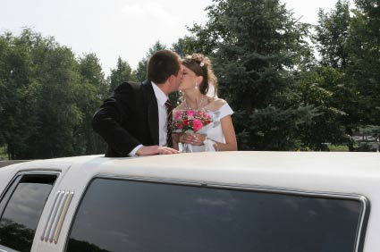 Bridegroom and bride are kissed in limousine